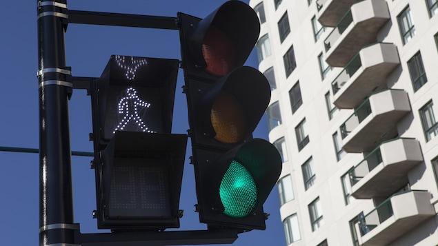Un feu pour piéton indique que les passants peuvent traverser puisque le petit bonhomme blanc est allumé. Le feu de circulation, lui, est au vert.