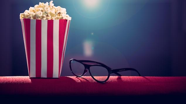 Du popcorn et des lunettes sur un fauteuil.