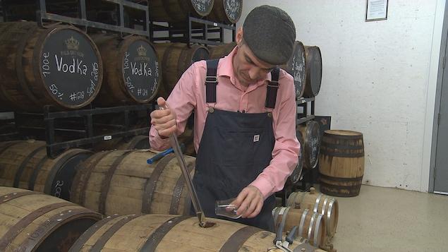 Sébastien Roy puise un alcool d'un baril