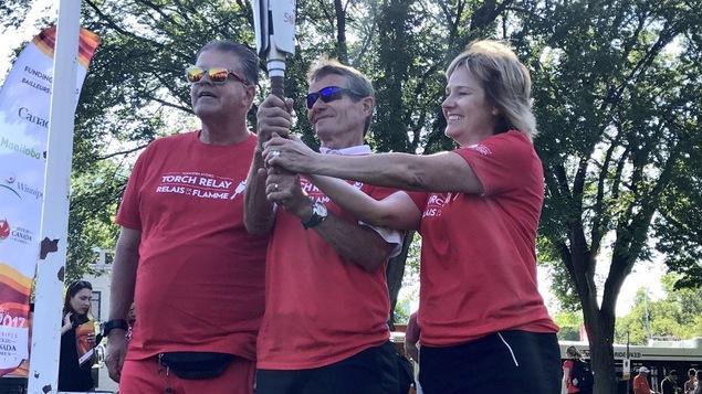 Trois porteurs sont côte à côte et tiennent la flamme des Jeux du Canada.