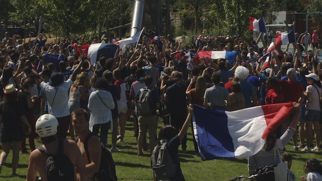 Des gens dans un parc avec des drapeaux bleu-blanc-rouge.