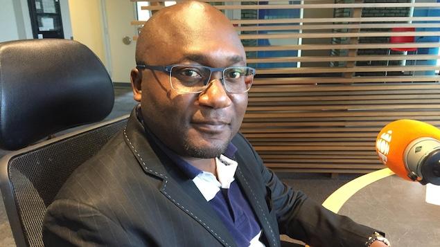 Un homme avec des lunettes pose devant un micro dans un studio de radio