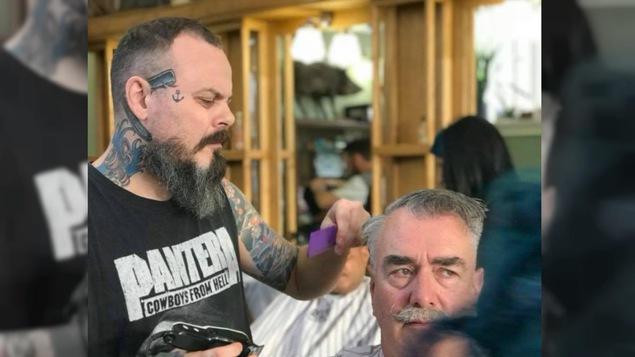 Un barbier taille les cheveux d'un homme.