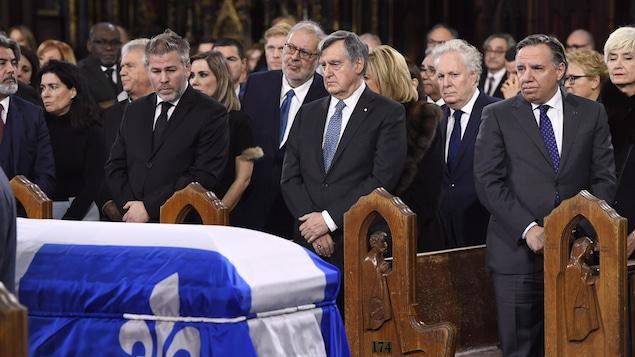 Pascal Bérubé, Lucien Bouchard et François Legault regardent le cercueil de Bernard Landry, recouvert d'un drapeau du Québec, à la basilique Notre-Dame.
