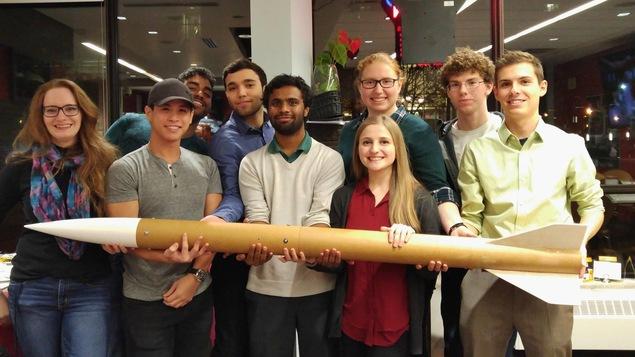 Un groupe de jeunes tiennent une fusée à bout de bras.