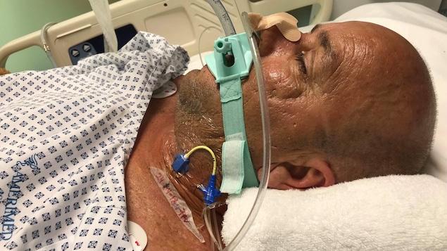 Un homme est intubé et est couché dans un lit d'hôpital.