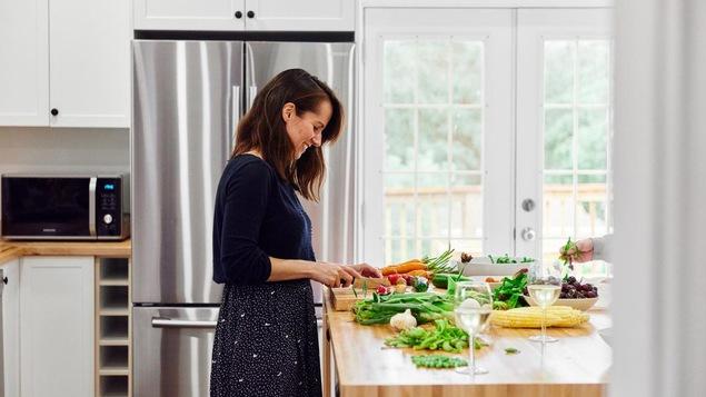 On voit la nutritionniste dans une cuisine aménagée. Elle coupe des légumes frais en souriant.
