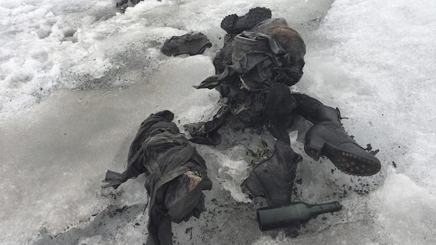Des restes de vêtements, de souliers et une bouteille en verre dans la neige