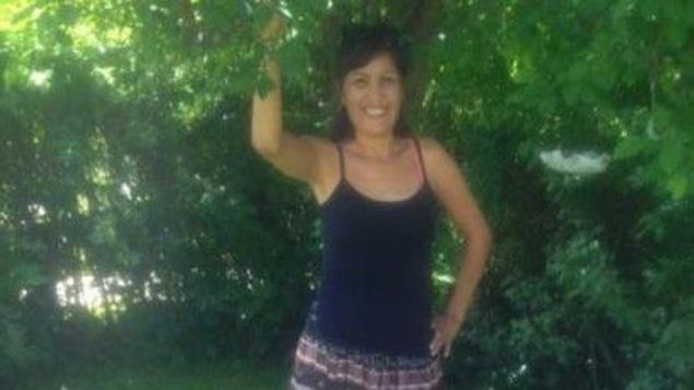 Une femme vêtue d'une longue jupe et d'un débardeur bleu sourit. Elle pose devant des arbres et a un bras en l'air.