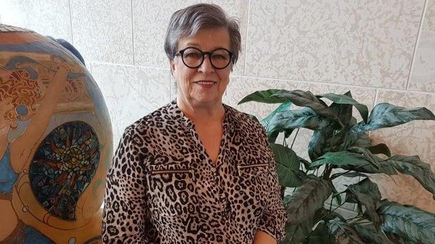 Une femme âgée aux cheveux courts et avec des lunettes rondes regarde l'objectif en souriant.