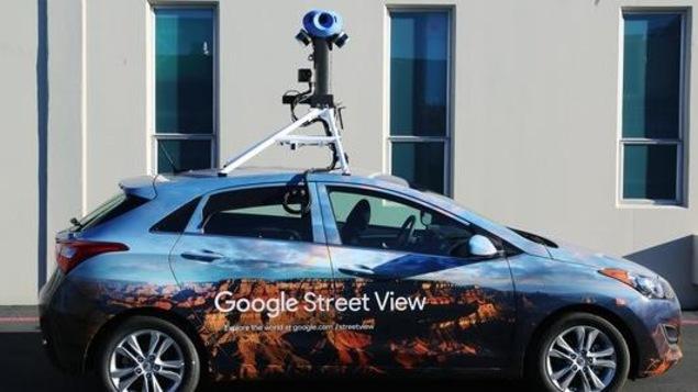 Une photo d'une voiture surmontée d'un appareil photo à 360 degrés et sur laquelle on peut lire « Google Street View ».