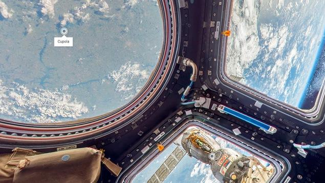Une photo montrant la vue de l'intérieur de l'observatoire de la station spatiale, qui contient un grand hublot circulaire entouré de hublots rectangulaires. On peut voir un module russe Soyouz à l'extérieur ainsi qu'une vue de la Terre.