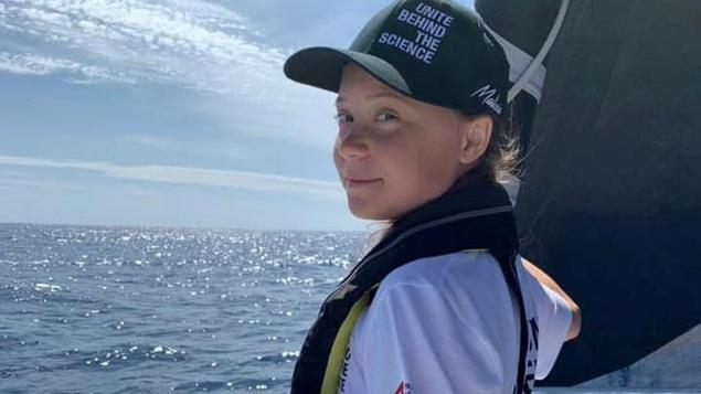 Greta Thunberg pose sur un bateau en mer.