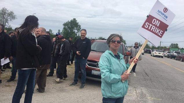 """Une femme tient un panneau qui dit """"On strike"""", une foule est en arrière d'elle."""