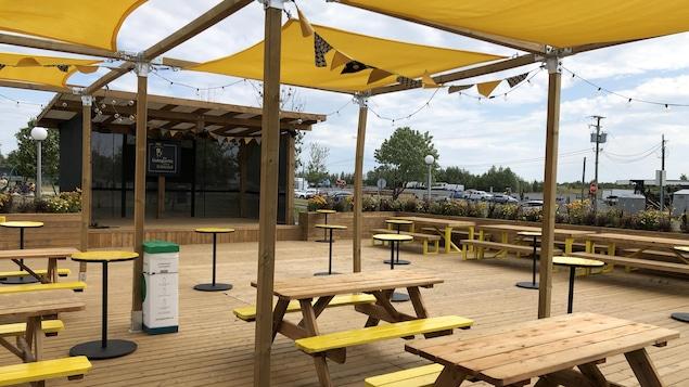 Une terrasse en bois avec des tables à pique-nique, des tables hautes et une scène.