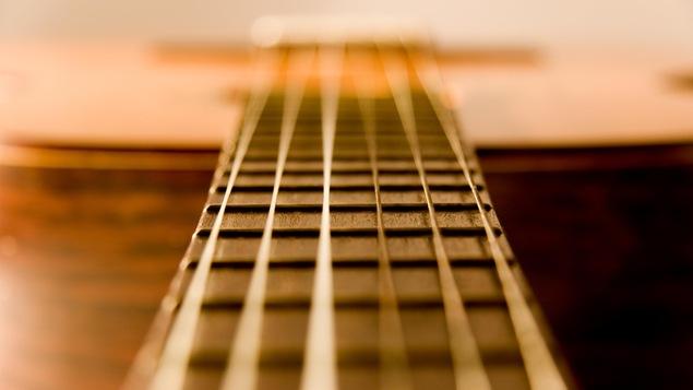 Les cordes d'une guitare acoustique vibrent.