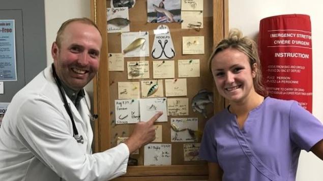Le Dr Adam Moir et Marina Wintle, qui étudie en sciences infirmières, devant ce que les médecins ont baptisé le « mur de la honte », et où sont exposés les hameçons retirés de pêcheurs maladroits.