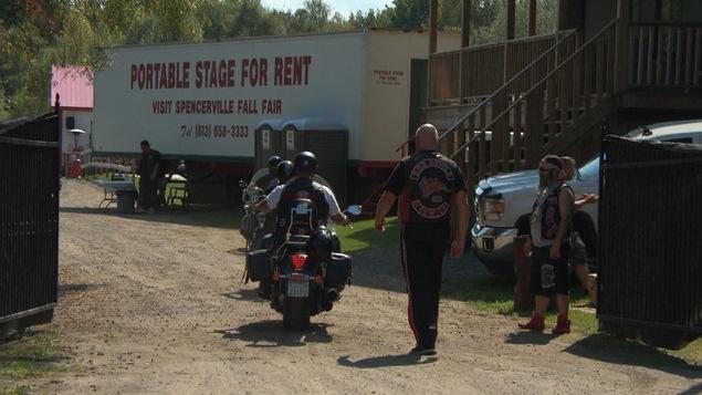 Des hommes à moto et d'autres à pied portant des vestons en cuir avec des logos de groupes de motards.
