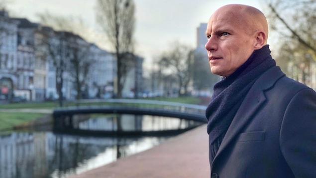 Un homme debout à l'extérieur, devant un canal