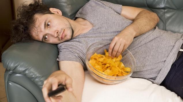 Un homme allongé sur un sofa mange des croustilles en regardant la télévision.