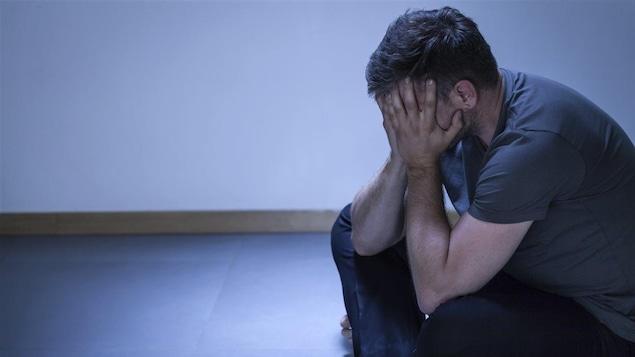Un homme en peine, assis par terre, se cache le visage avec ses mains