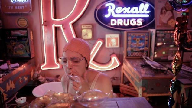 Une femme porte des lunettes, fume et porte un bonnet de bain sur la tête.