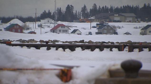 Des maisons en bordure d'un quai en hiver.