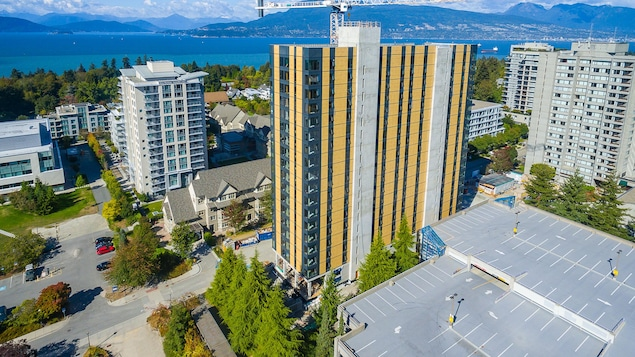 Une vue de haut sur l'immeuble de 18 étages avec l'océan et les montagne en arrière plan.