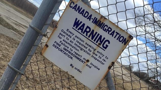 Une clôture avec une enseigne de mise en garde.