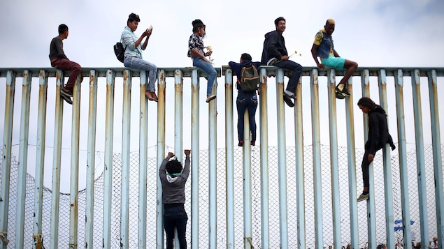 Des Mexicains escaladent une barrière qui sépare le Mexique et les États-Unis en avril 2018.