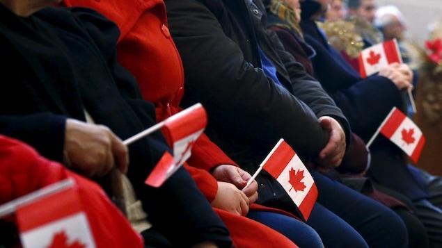 Des personnes dont on ne voit pas le visage sont assises et tiennent dans leurs mains un drapeau canadien.