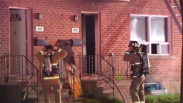 Deux pompiers devant une résidence qui est la proie des flammes.