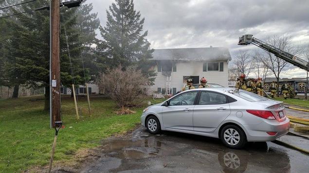 Une voiture devant une maison en flammes