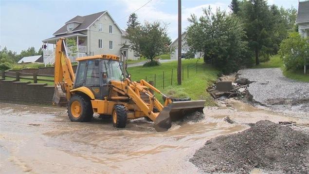 Un tracteur au milieu de l'eau dans une rue inondée