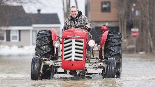 Un homme conduit un tracteur sur une rue inondée