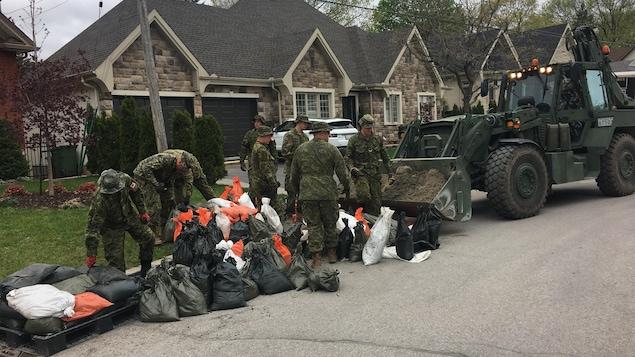 Huit soldats ramassent des sacs de sable, rue Cartier, à Gatineau.