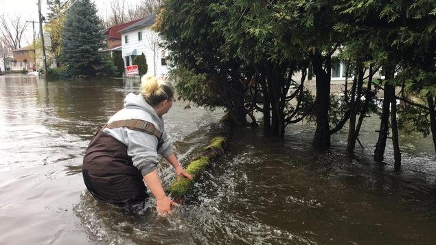 Une femme redirige un billot de bois. Elle a de l'eau jusqu'à la taille.