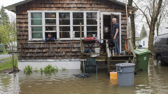 Deux hommes accompagnés d'un chien surveillent l'eau qui commence à inonder leur maison.