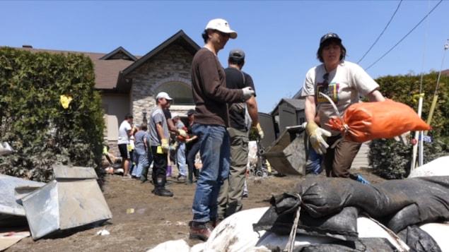 Des bénévoles forment une chaîne humaine pour retirer des sacs de sable.