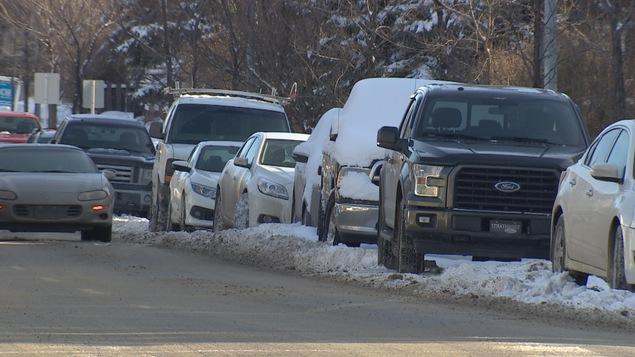 Une série de véhicules stationnés les uns derrière les autres sur le côté d'une rue.