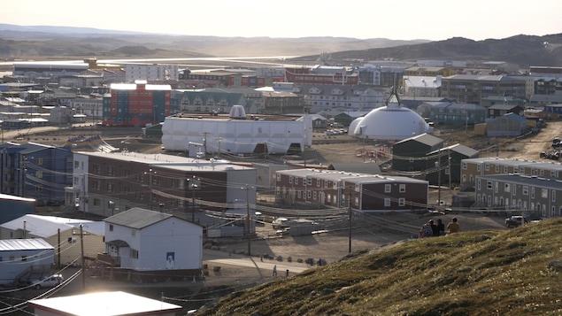 Une prise de vue d'Iqaluit, la capitale du Nunavut, depuis une colline, ce qui permet de voir une série d'immeubles.