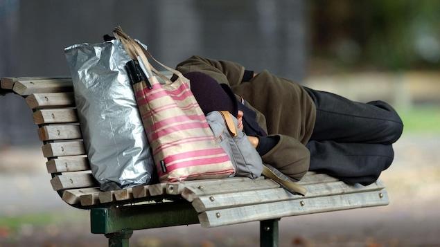 Un homme dort sur un banc de parc, ses effets personnels tenant dans quelques sacs.