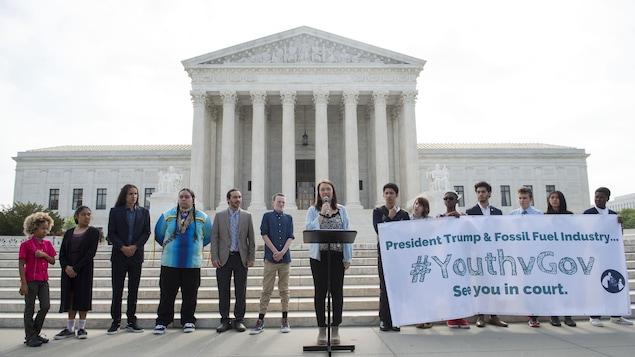 Quatorze jeunes dont une qui parle au microphone et sept qui tiennent une grande affiche, devant les marches de la Cour Suprême des États-Unis à Washington.
