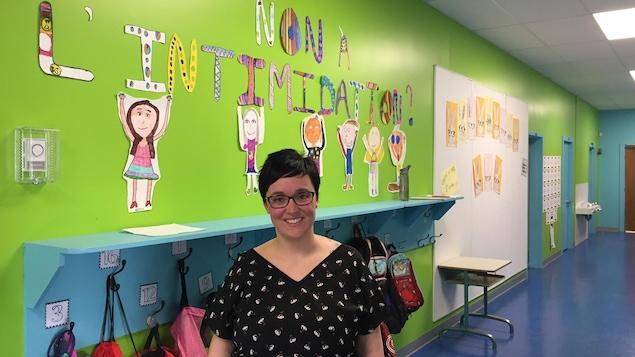 Une enseignante pose dans le couloir d'une école primaire.