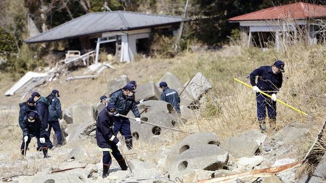 Des policiers procèdent à des opérations de recherche à Tomioka dans la région de Fukushima.