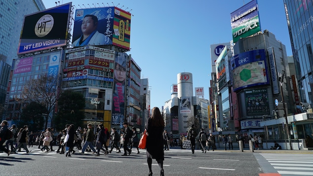 Une femme traverse le célèbre carrefour de Shibuya à Tokyo.