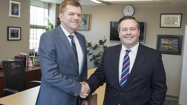 Première poignée de main entre le  chef du Wildrose Brian Jean et celui du Parti conservateur Jason Kenney