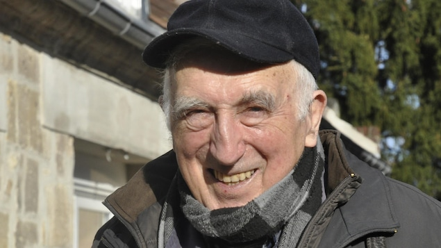 Un homme souriant avec une casquette à l'extérieur devant une maison.