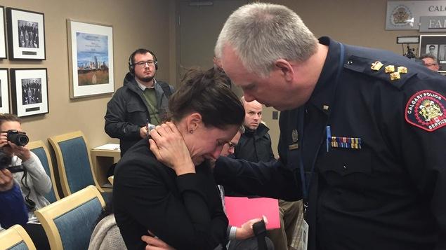 Le chef Roger Chaffin, à gauche, réconfortant l'officière Jen Magnus après qu'elle a remis sa démission lors des audiences de la commission de police de Calgary.