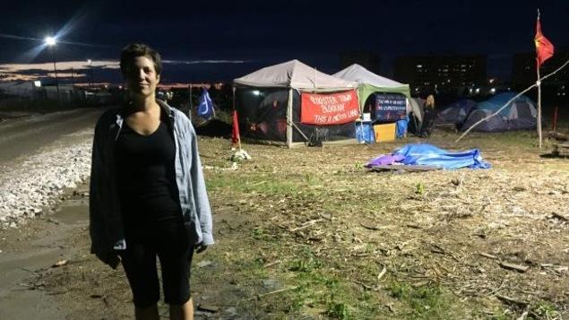 Jenna Vandal est debout à gauche de l'image. Au loin, il y a des tentes sur un site de camping improvisé.